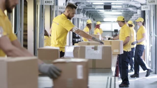 vídeos de stock, filmes e b-roll de trabalhadores dos correios pacotes na esteira de triagem - correio correspondência