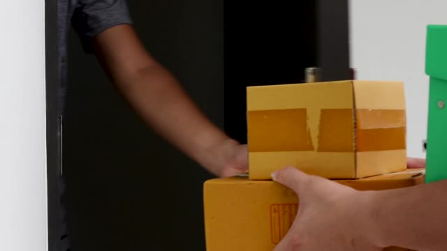 Postman delivering package of goods to home, Close up man hands signing to get his package from delivery man, Home delivery concept, Deliver packages to recipients quickly, complete products.