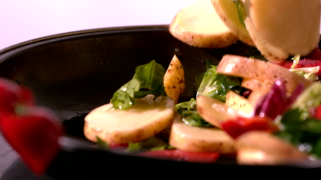 Potato and salad falling in a pan video