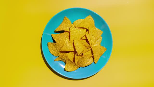 kartoffelchips, die von einem blauen teller entfernt werden. stoppen sie die bewegung. ansicht von oben. - abwesenheit stock-videos und b-roll-filmmaterial