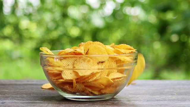 potato chips falling into transparrent glass bowl standing on table in garden slow motion potato chips falling into transparrent glass bowl standing on table in garden slow motion potato chip stock videos & royalty-free footage