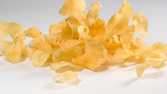 Potato Chips falling onto a white surface in slow motion Potato Chips falling onto a white surface in slow motion potato chip stock videos & royalty-free footage