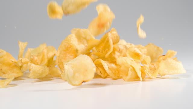 vidéos et rushes de croustilles de pomme de terre tombant sur une surface blanche au ralenti - croustillant
