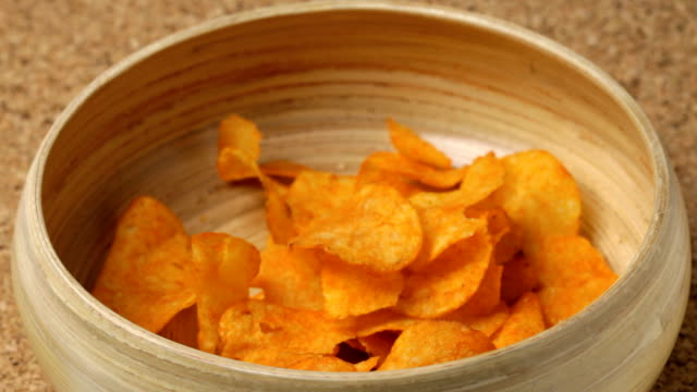 Potato chips Close up of paprika potato chips falling into bowl. No sound. potato chip stock videos & royalty-free footage