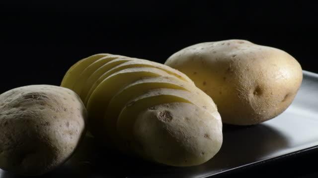 potato cut gyrating on a black tray on black background. solanum tuberosum - group of people filmów i materiałów b-roll