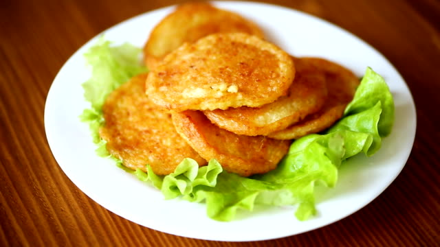 potato pancakes with lettuce leaves in a plate potato pancakes with lettuce leaves in a plate on a wooden table russian culture stock videos & royalty-free footage