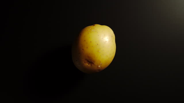 top view: potato rotates on a black surface - stop motion - patate video stock e b–roll