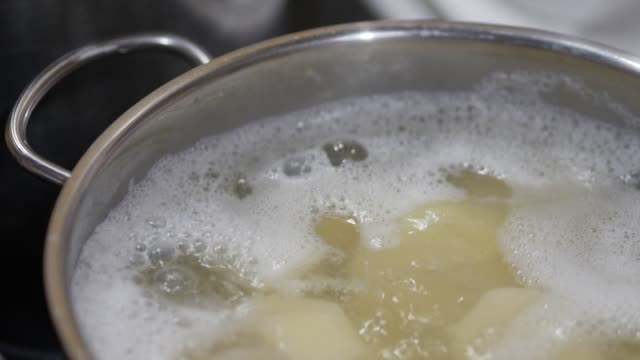 potatoes are boiled in boiling water - bollente video stock e b–roll