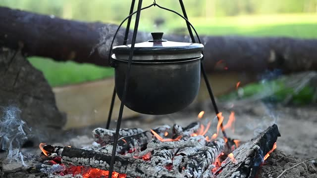 Potatoes are boiling in a pot over the fire. Cooking in the campaign
