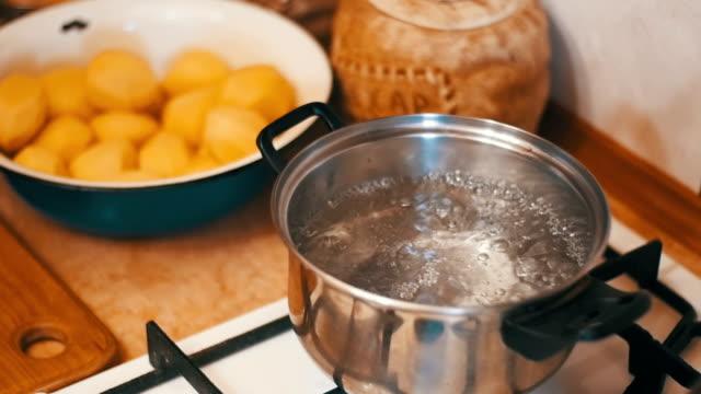 家庭の台所で水を沸騰の鍋にジャガイモ ハエ。スローモーション - ローフード点の映像素材/bロール