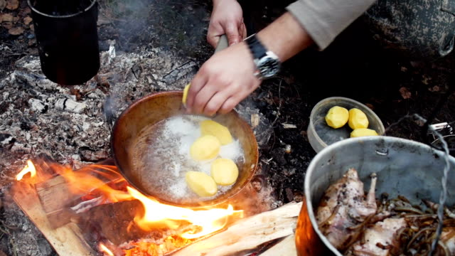 Potatoes fried in a pan in outdoor video