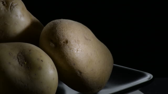 potatoes vegetables in a mountain gyrating on a black tray. solanum tuberosum - клубень стоковые видео и кадры b-roll