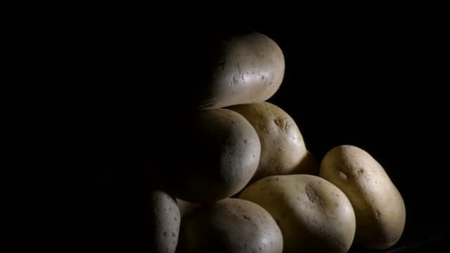 potatoes vegetables in a mountain on a black tray. solanum tuberosum - group of people filmów i materiałów b-roll