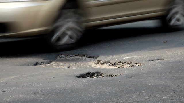 Pothole on the road Potholes on the old highway in the city negative emotion stock videos & royalty-free footage