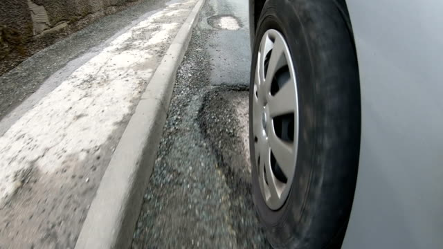 4K: Potholes on very damaged road - Driving over, view from the Tyre
