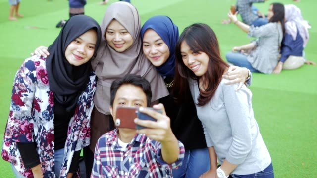potrait of happy south east asian man and women doing selfie in the park with two kind of tones - abbigliamento religioso video stock e b–roll
