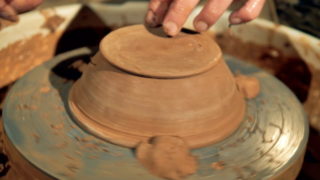 A potter carves the foot of a new bowl. video