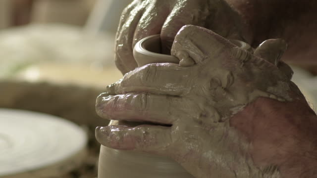 potter craftsman molding the neck and mouth of a new vase in mud in the lathe - станок стоковые видео и кадры b-roll