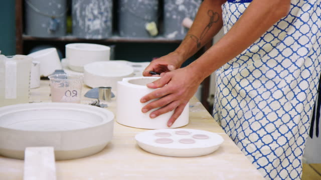 Potter making clay pots in pottery studio