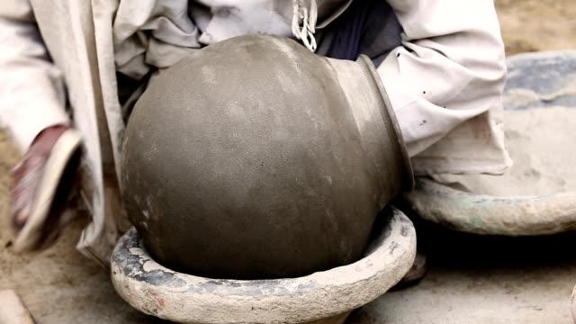 potter molding a shape at workshop