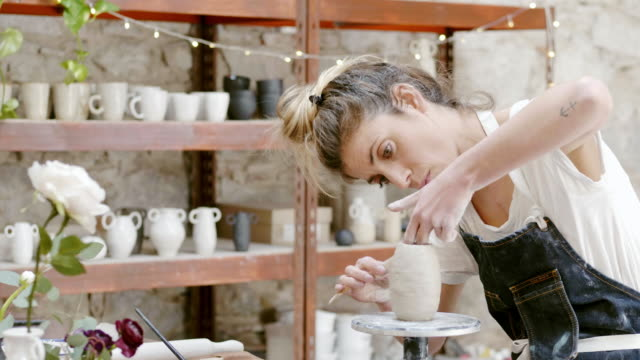 Potter shaping vase with work tool at studio Lockdown shot of female potter shaping vase with work tool. Confident woman is doing pottery in workshop. They are at studio. hobbies stock videos & royalty-free footage