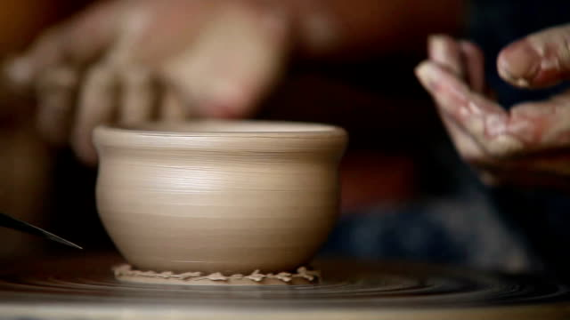 Potter works with clay bowl in workshop video