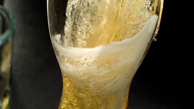 pouing bier ins glas. bläschen und schaum - alkoholfreies getränk stock-videos und b-roll-filmmaterial