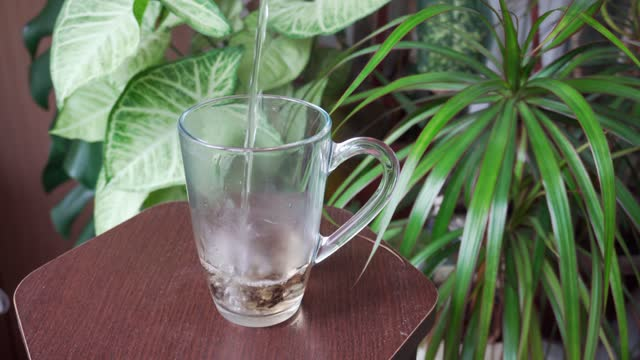 Pour fragrant hot tea into a transparent cup. Healthy and tasty breakfast.