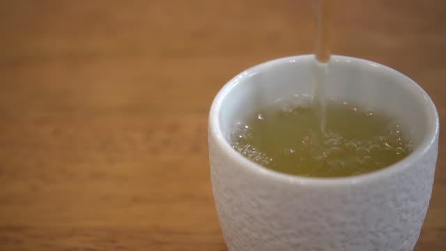 gießen hot tea into cup truck shot - grüner tee stock-videos und b-roll-filmmaterial