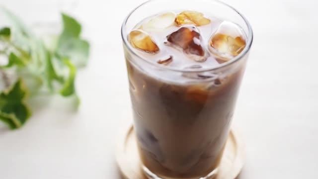 vídeos de stock e filmes b-roll de pour milk to a glass of ice coffee - café gelado