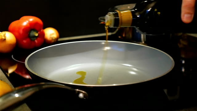 pour olive oil into a pan, slow motion - olio d'oliva video stock e b–roll
