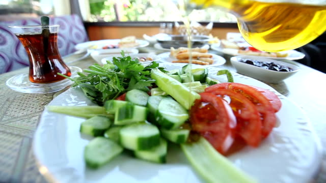 pour olive oil over tomatoes at Turkish breakfast table video