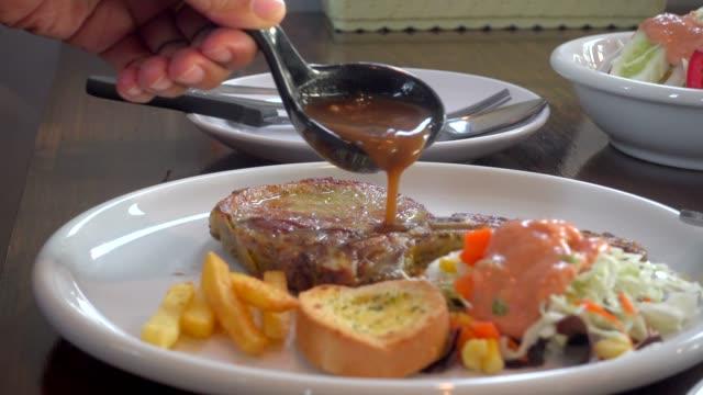 vídeos de stock e filmes b-roll de pour sauce on steak - meat plate