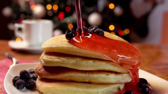vídeos de stock e filmes b-roll de pour strawberry syrup pancakes with blueberries - christmas cake