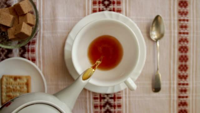 オーバーヘッドのショット カップに紅茶を注ぐ - お茶の時間点の映像素材/bロール