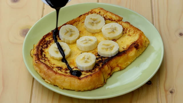 vídeos de stock e filmes b-roll de pour the chocolate on french toast with banana, apple and orange - roasted toast