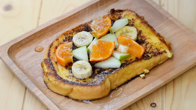 vídeos de stock e filmes b-roll de pour the icing sugar on french toast with banana, apple and orange - roasted toast