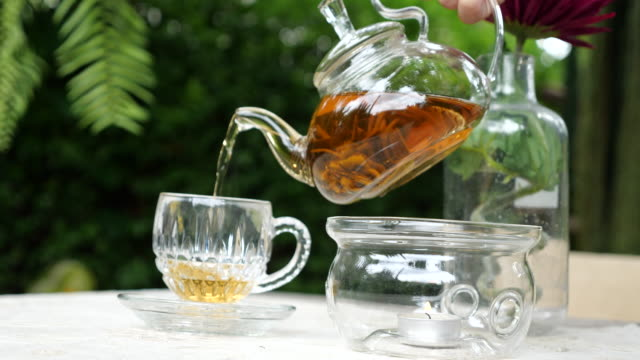 pour the tea into a glass. - tea cup stock videos & royalty-free footage