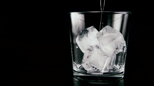 pour vodka into the ice. slow mo - алкоголь напиток стоковые видео и кадры b-roll