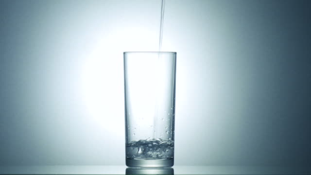 Pour water into glass. - video