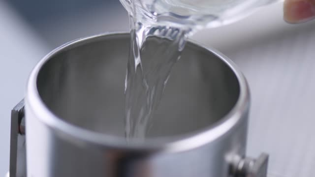Pouring a chemical fluid into a metal container Pouring a chemical fluid into a metal container beaker stock videos & royalty-free footage