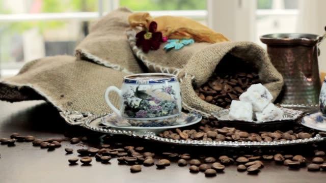 bir fincan sıcak kahve dökme ve kavrulmuş kahve çekirdekleri dönüm masada sl video
