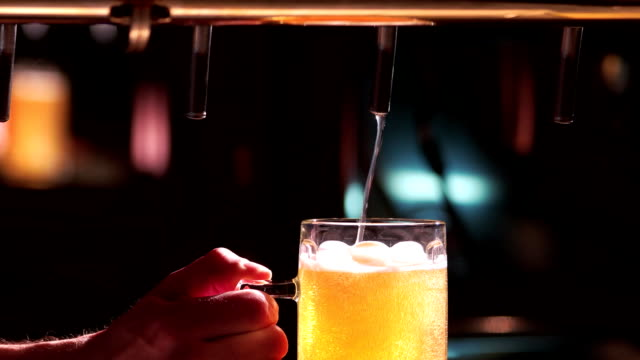 Pouring a glass of beer with little foam. video