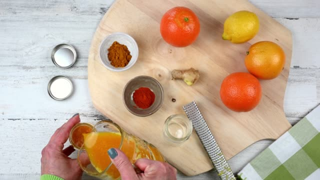 pouring a glass of vitamin C packed citrus juice drink overhead view of woman making homemade vitamin C drink to boost immunity ginger spice stock videos & royalty-free footage