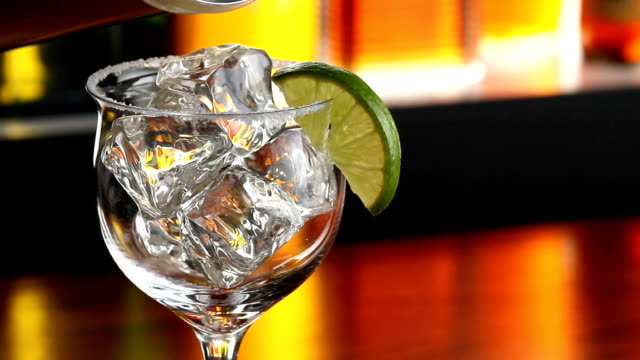 Pouring a Margarita A cold refreshing margarita is poured into a glass in a bar margarita stock videos & royalty-free footage