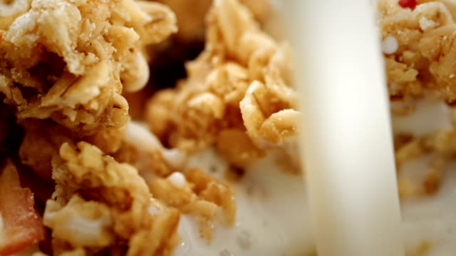 vídeos de stock e filmes b-roll de pouring a milk into a bowl of breakfast cereals - oats