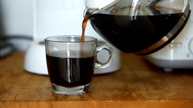 vídeos y material grabado en eventos de stock de verter una taza de café caliente de un pote de cristal en la mañana en casa. - café negro