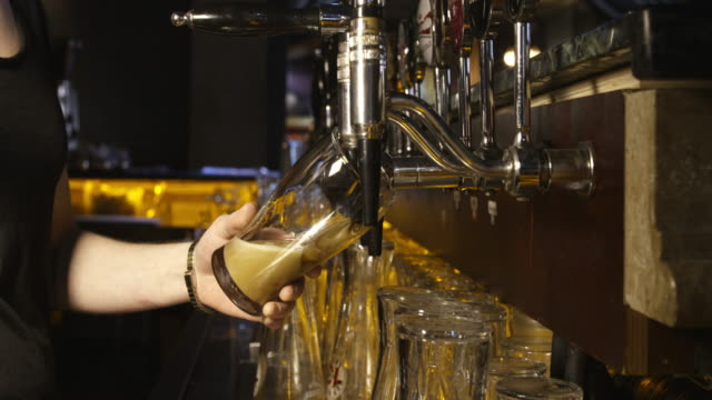 pouring a pint of guinness from beer tap in pub video
