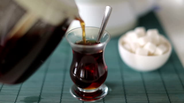Pouring and stirring cup of traditional Turkish tea - chai video
