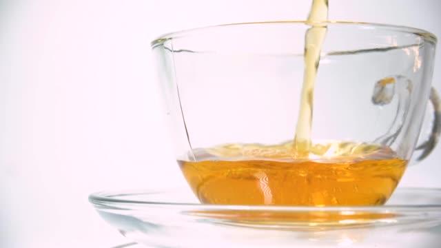 白い背景のクローズアップに一致する透明なガラスティーカップにティーポットから香り紅茶を注ぐ - マグカップ点の映像素材/bロール